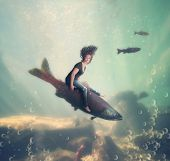 stock photo of steelhead  - a pretty woman riding a fish under the water of an ocean or sea - JPG