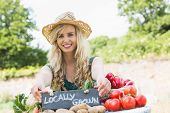 stock photo of stall  - Happy young female farmer standing at her stall at the farmers market smiling at the camera - JPG