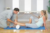 picture of physiotherapist  - Physiotherapist examining patients foot while sitting on floor in bright room - JPG