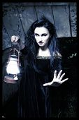 stock photo of gothic hair  - Gothic girl standing with a lantern in his hand at the bridge
