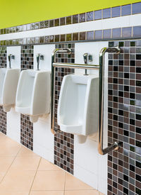 stock photo of crippled  - White Porcelain Urinals for Cripple and Old People in Public Toilet - JPG