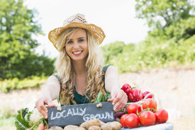 image of stall  - Happy young female farmer standing at her stall at the farmers market smiling at the camera - JPG