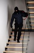 stock photo of bandit  - Bandit on stairs with a gun and bag with the loot - JPG