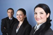 stock photo of semi-formal  - Cheerful group of three business people standing in semi profile and looking at you showing satisfaction and happiness - JPG