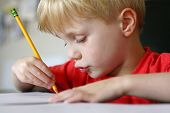 pic of dimples  - a cute young child is making a funny face as he is concentrating at drawing on paper with a pencil - JPG