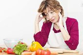 picture of stereotype  - Tired mature woman of preparing meals in the kitchen - JPG