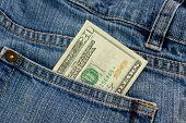 foto of twenty dollars  - A twenty dollar bill sticking out the front pocket of denim blue jeans - JPG