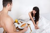 stock photo of bed breakfast  - Young man bringing breakfast in bed to his wife