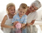 stock photo of save money  - Smiling grandmother and children saving money in a piggybank - JPG