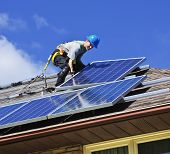 foto of generator  - Man installing alternative energy photovoltaic solar panels on roof - JPG