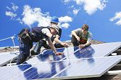 picture of generator  - Workers installing alternative energy photovoltaic solar panels on roof - JPG