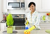 stock photo of disinfection  - Smiling young black woman with sponge and rubber gloves cleaning kitchen - JPG