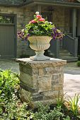 image of planters  - Stone planter with flowers near driveway of house - JPG