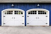 picture of quaint  - Two white garage doors with windows on blue house - JPG