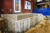 stock photo of home addition  - Building addition to residential house with new foundation - JPG