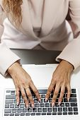 Female hands typing on laptop keyboard from above