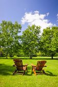 foto of lawn chair  - Two wooden adirondack chairs on lush green lawn with trees - JPG