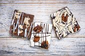 Three assorted chocolate caramel bark pieces as sweet dessert arranged on wooden background from abo