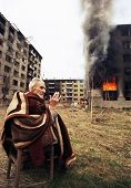 SARAJEVO, BOSNIA - MAR 18: An ethnic Croatian man prays outside his burning apartment on the last da