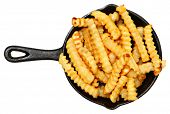 Oven Baked Crinkle Fries in Cast Iron Skillet over white.