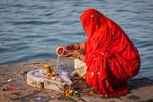 stock photo of pooja  - Indian woman performs morning pooja on sacred river Narmada ghats in Maheshwar - JPG