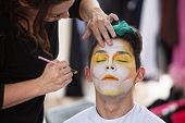 picture of clown face  - Young male clown getting makeup on face - JPG