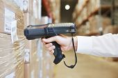 foto of dispatch  - worker hand man scanning package with warehouse barcode scanner in modern storehouse - JPG