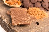 pic of bonbon  - Close up of milk chocolate bar shredded chocolate and bonbons on a wooden table selective focus - JPG