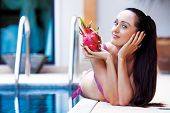 stock photo of woman dragon  - beautiful slim young  woman by the swimming pool with a dragon fruit - JPG