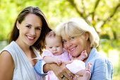 pic of mother baby nature  - Portrait of a mother and grandmother smiling with baby outdoors - JPG