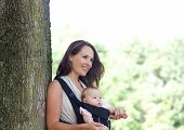 stock photo of infant  - Portrait of a mother smiling with infant in baby carrier - JPG