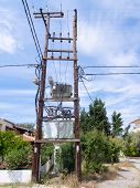 stock photo of electricity pylon  - Electricity sub station on wooden pylons in a small village - JPG
