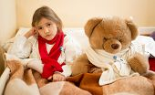 pic of temperature  - Little sad girl measuring temperature with teddy bear in bed - JPG
