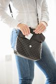 stock photo of condom  - Conceptual photo of young woman getting ready for date and putting condom in handbag - JPG