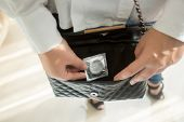pic of venereal disease  - Closeup photo of young woman putting condom in handbag - JPG