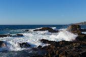 foto of shoreline  - Ocean waves comming to cliff and breaking on shoreline stones - JPG