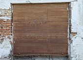 stock photo of roller door  - Old rusty roller doors in a side wall of a house - JPG