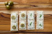 stock photo of brie cheese  - close up of slices of brie cheese on everything crackers with sliced of olives and fresh dill - JPG