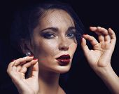 stock photo of grieving  - beauty brunette woman under black veil with red manicure close up - JPG
