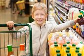 image of supermarket  - smiling positive boy at the supermarket with shopping cart and choosing juice - JPG