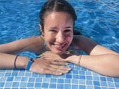 foto of teen pony tail  - A teen girl resting at the edge of a swimming pool - JPG