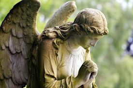 foto of pray  - A large stone angel praying in colour - JPG