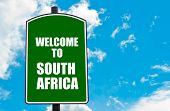 foto of south-pole  - Green road sign with greeting message WELCOME TO SOUTH AFRICA isolated over clear blue sky background with available copy space - JPG