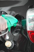 pic of fuel economy  - Male hand refilling the black car with fuel on a filling station - JPG