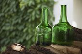 image of green wall  - Antique bottles of green glass are on the chopping wood - JPG