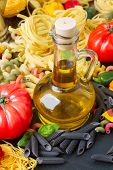picture of olive shaped  - Jar of Olive oil with raw pasta and tomatoes - JPG