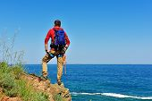 foto of mountain-climber  - rock climber with backpack on top of mountain looking to sea - JPG