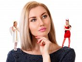 stock photo of hells angels  - Beautiful young woman with small angel and demon on her shoulders isolated over white background - JPG