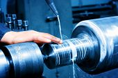 stock photo of turn-up  - Worker measuring on industrial turning machine at work - JPG