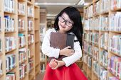 stock photo of indian apple  - Portrait of little elementary school student standing in the library while holding a book and apple - JPG